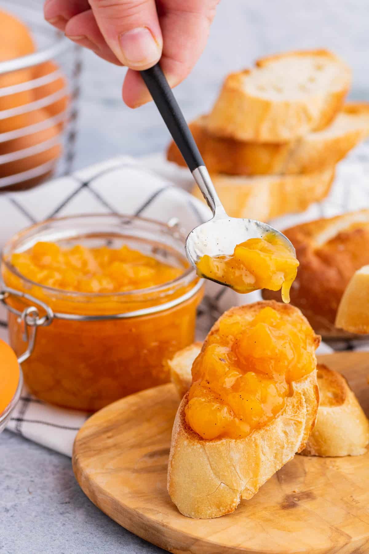 A hand holds a spoon full of Peach Freezer Jam over a slice of toast.