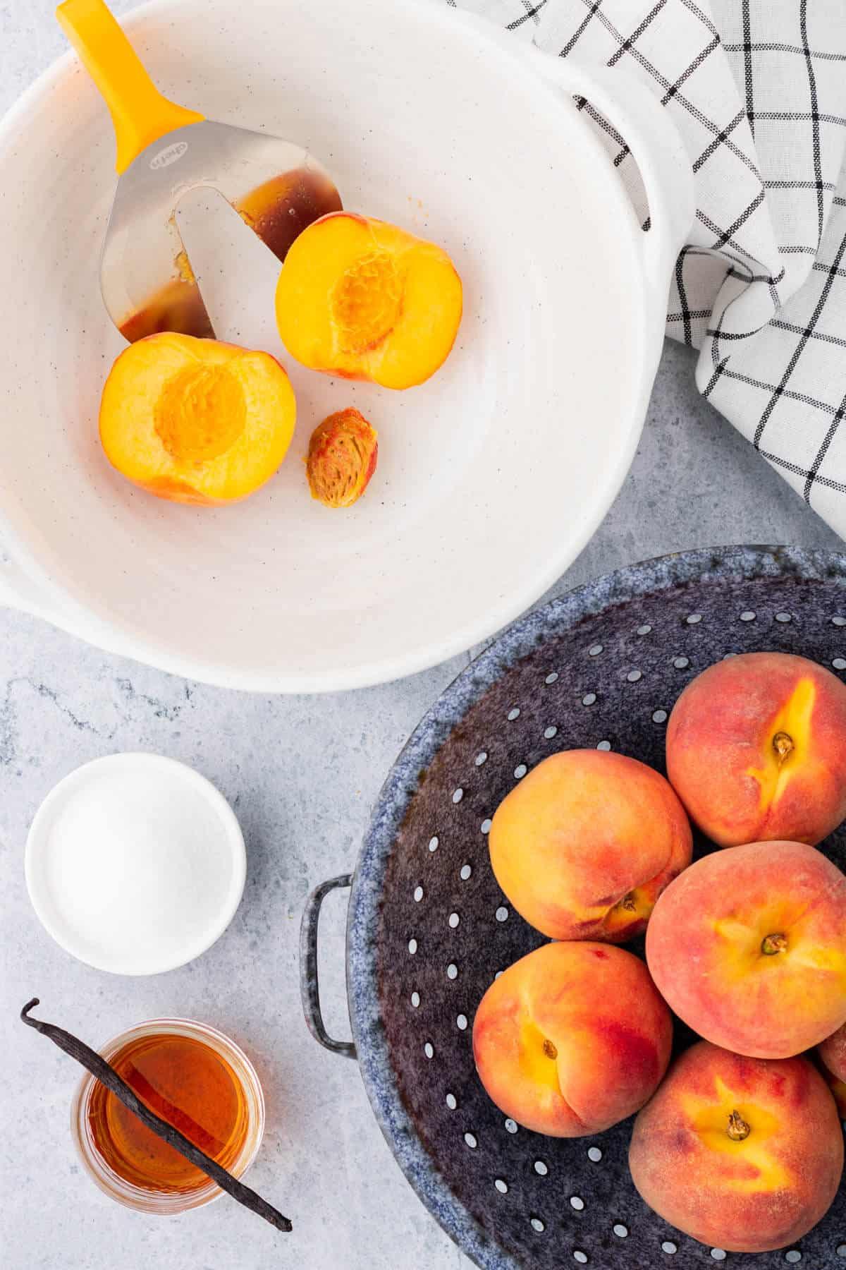 A split peach in a white bowl with a peach splitter tool.