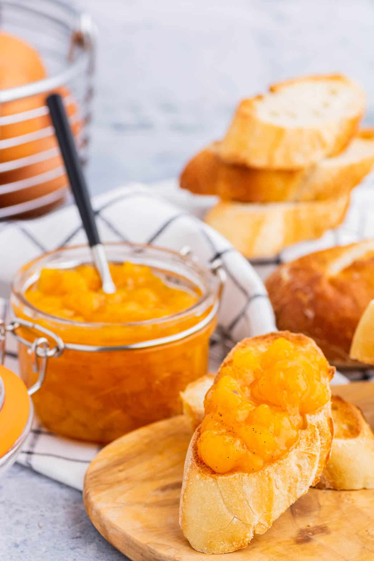 A toast covered in bright orange Peach Freezer Jam in front of a jar of the same jam.