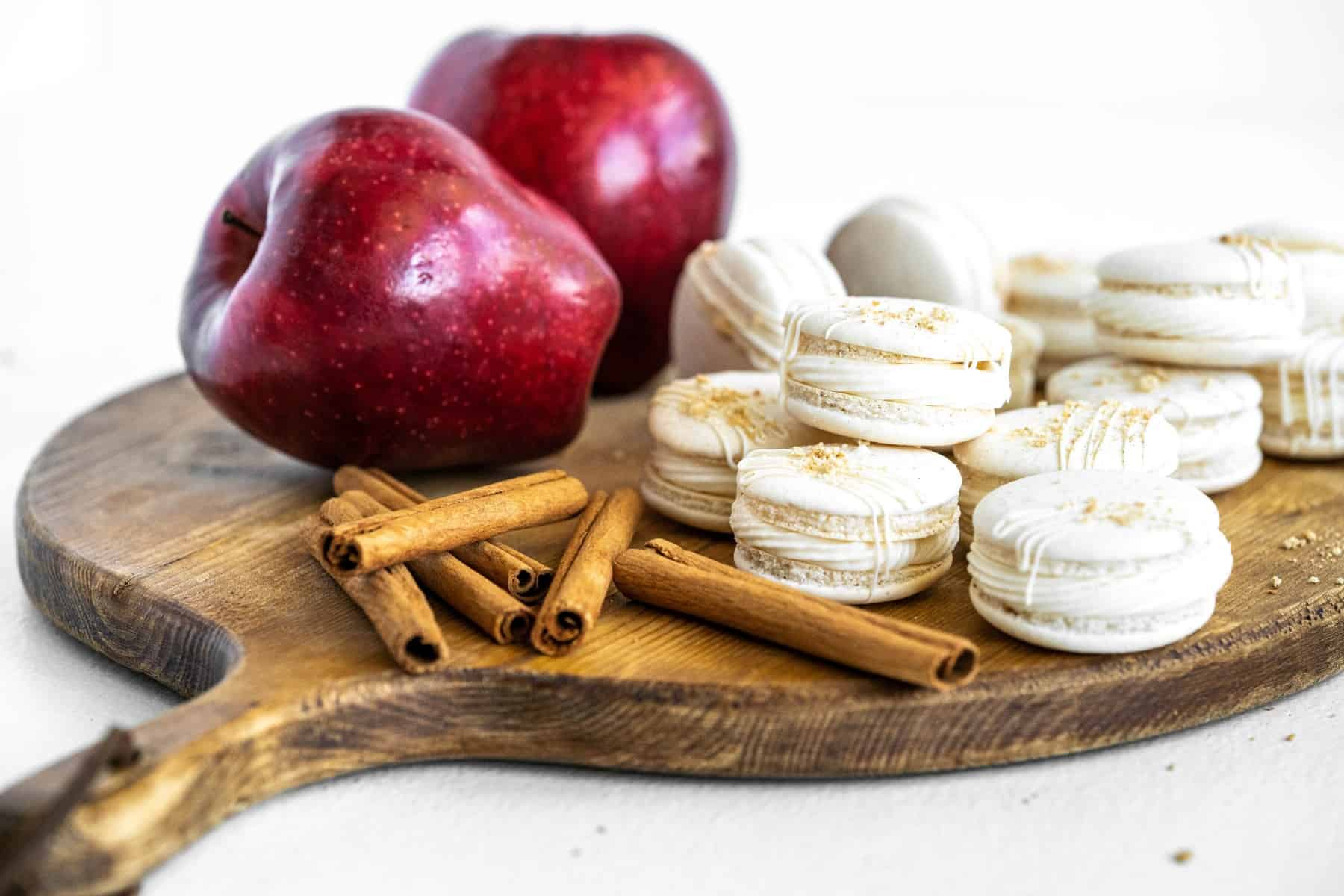 Macarons with apples and cinnamon sticks on a wooden board