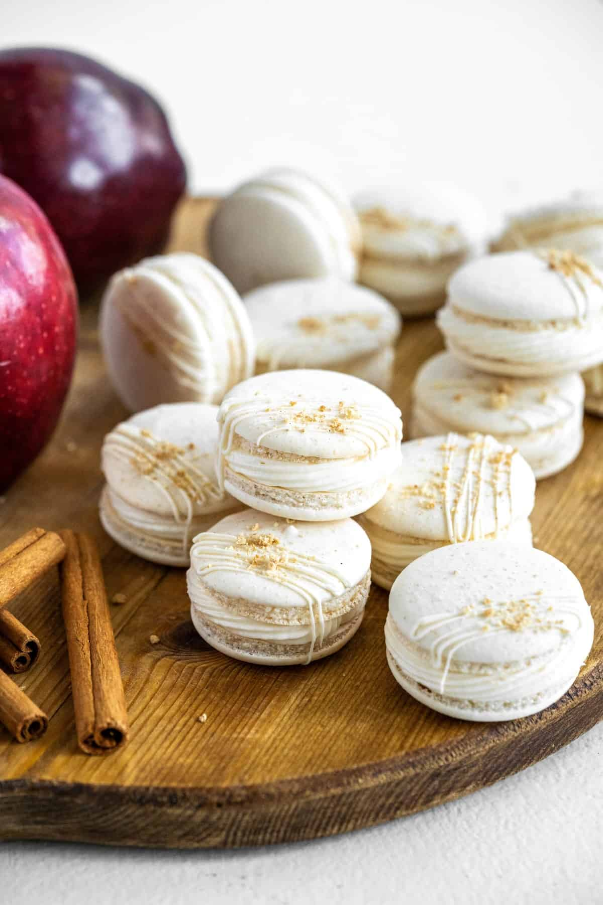 Macarons on a wooden board with apples and cinnamon sticks