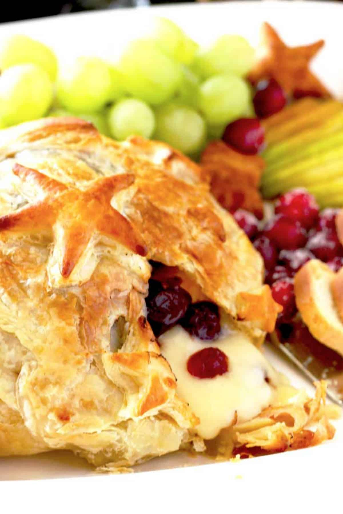 Baked brie oozing out of puff pastry with cranberries
