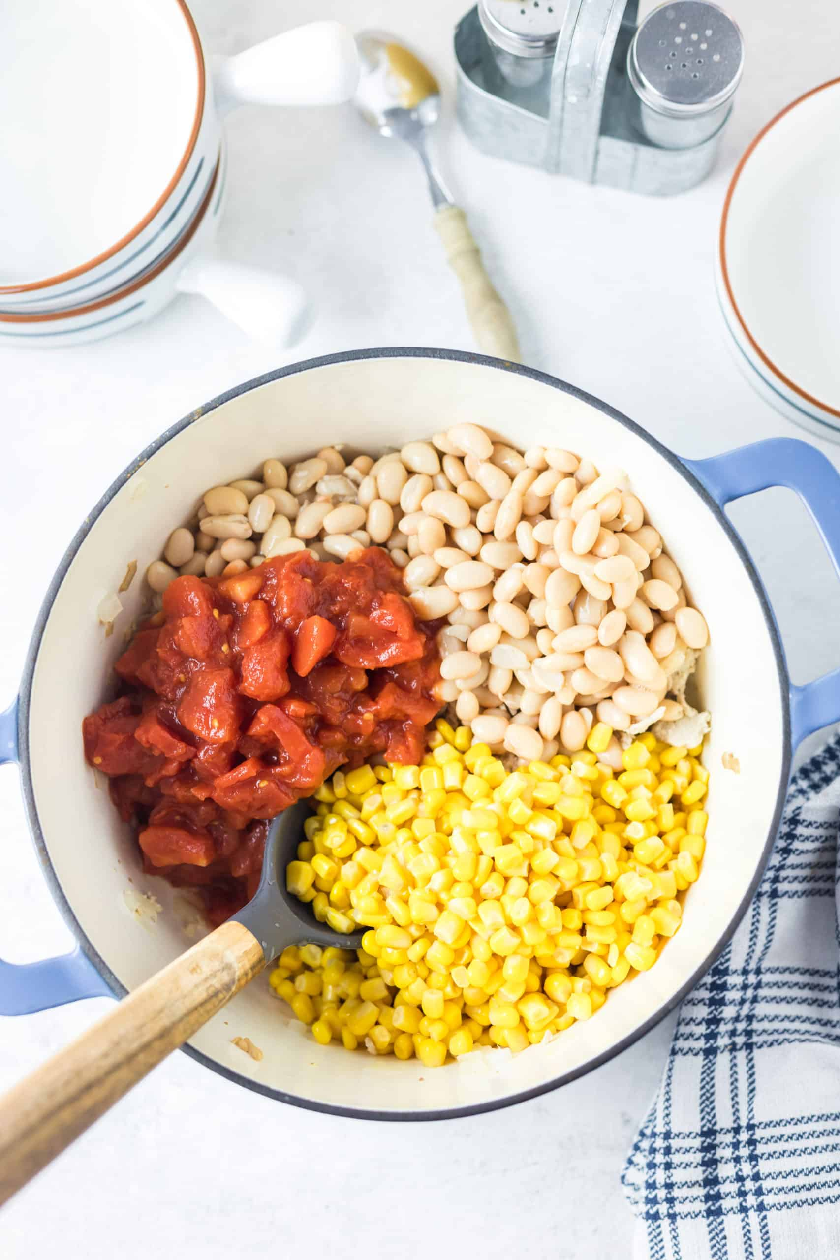 White beans, diced tomatoes and corn added to cooked chicken in a pot.