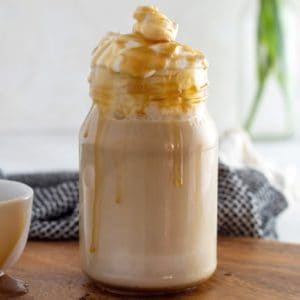 Copycat Starbucks Caramel Macchiato topped with whipped cream and caramel sauce in a jar glass
