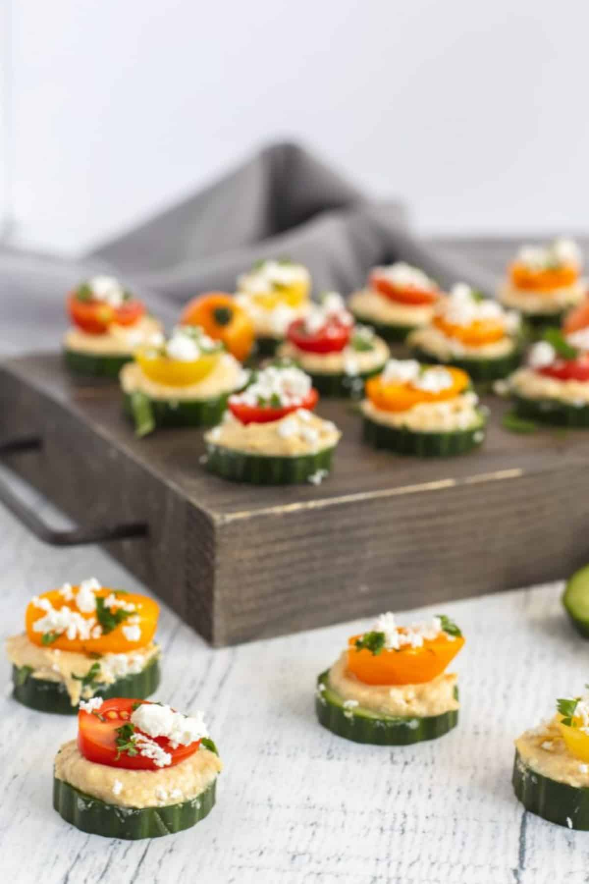 Cucumber hummus bites on a wooden board and wooden counter top.