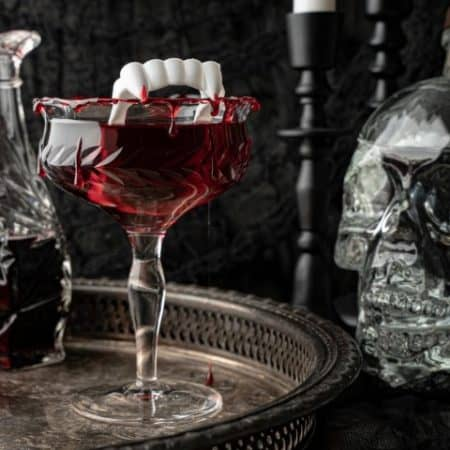 Dracula's Kiss - Halloween Cocktail on a silver tray with decanters and a glass skull on the side.