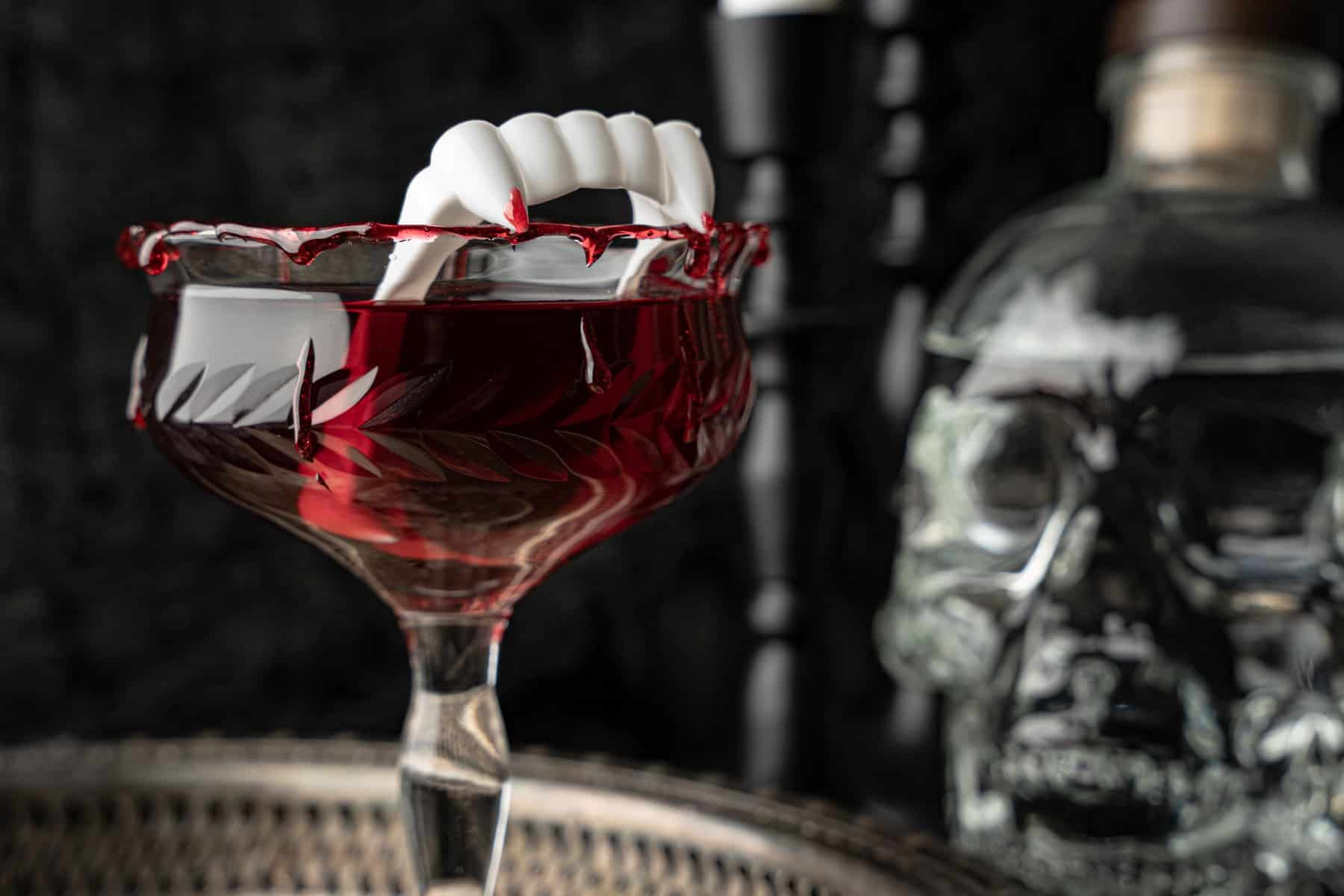 Horizontal shot of a Dracula's Kiss cocktail with vampire teeth inside the glass