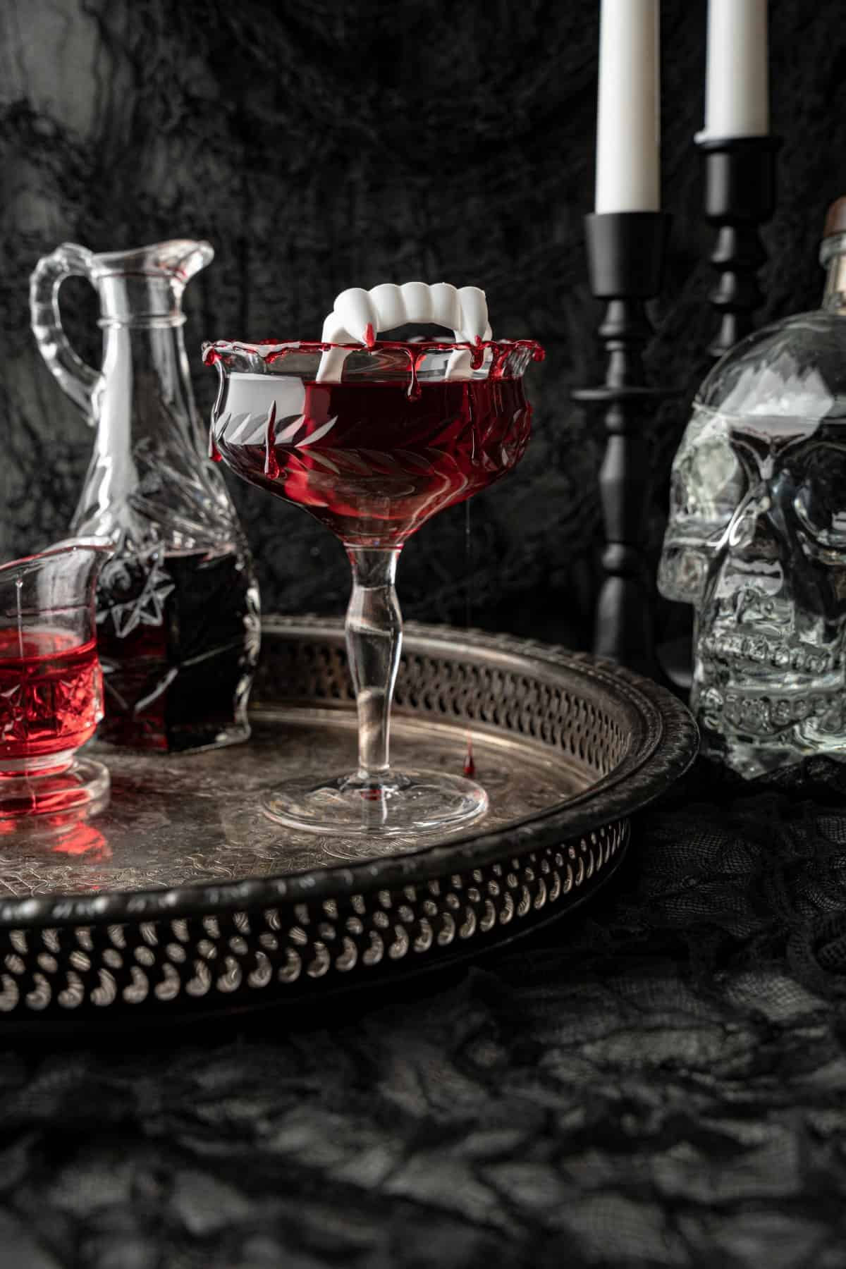 Dripping blood from a Dracula's Kiss cocktail on a silver tray with a glass skull, candles and other decanters.