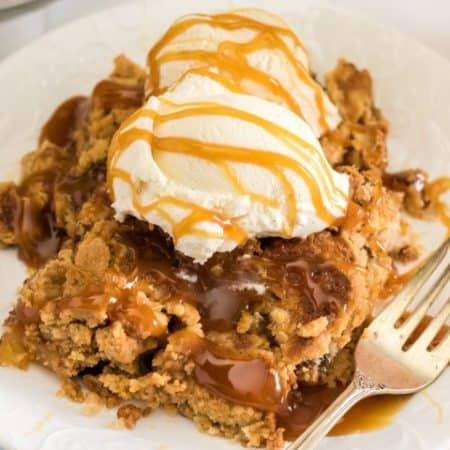Apple Dump Cake on a plate with ice cream and caramel sauce