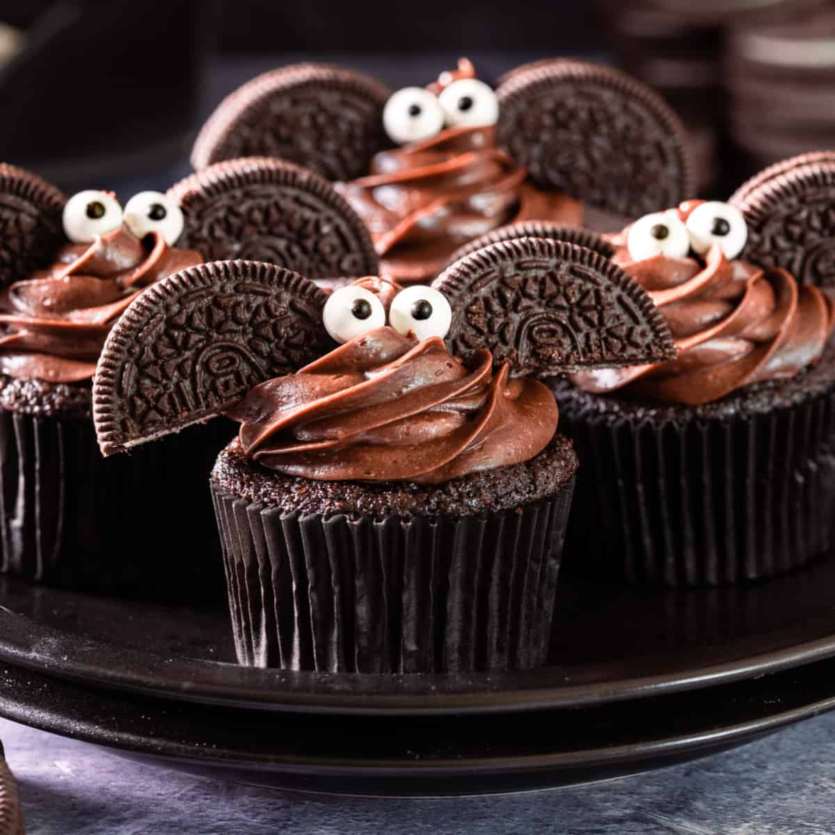 Halloween cupcakes on a black plate.