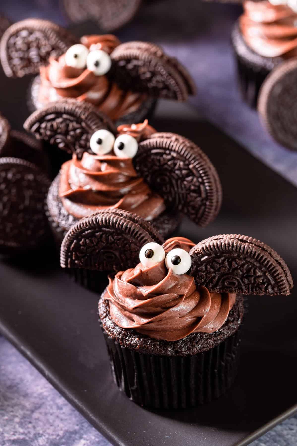 Bat cupcakes on a long black platter