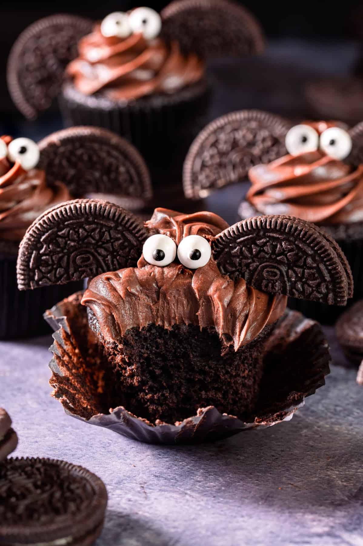 A large bite taken from a chocolate bat Halloween cupcake