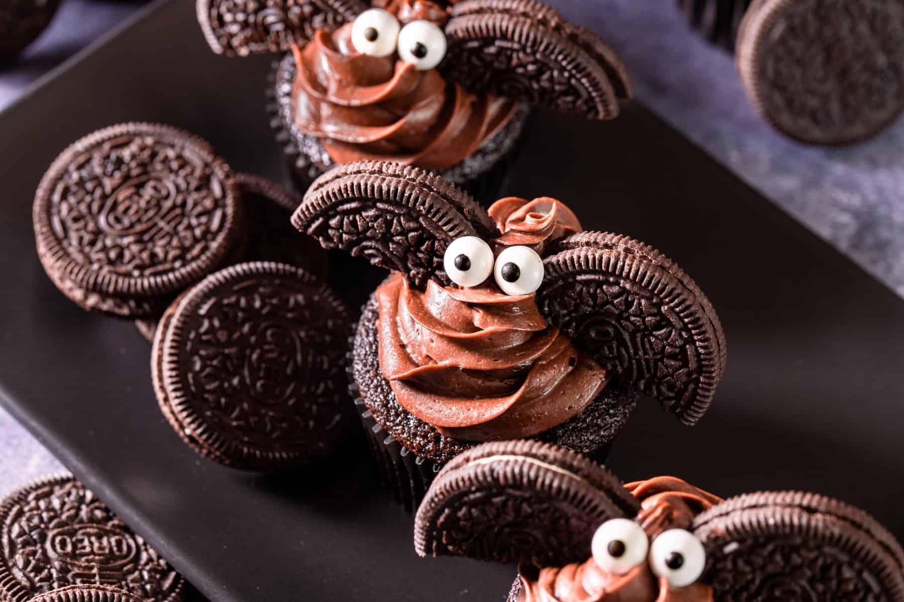 Overhead horizontal shot of bat cupcakes on a long black plate.