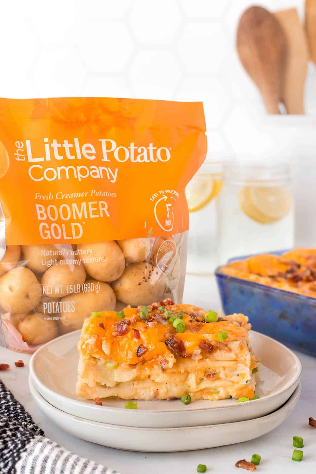 Plated slice of pierogi casserole with a bag of Little Potatoes behind.