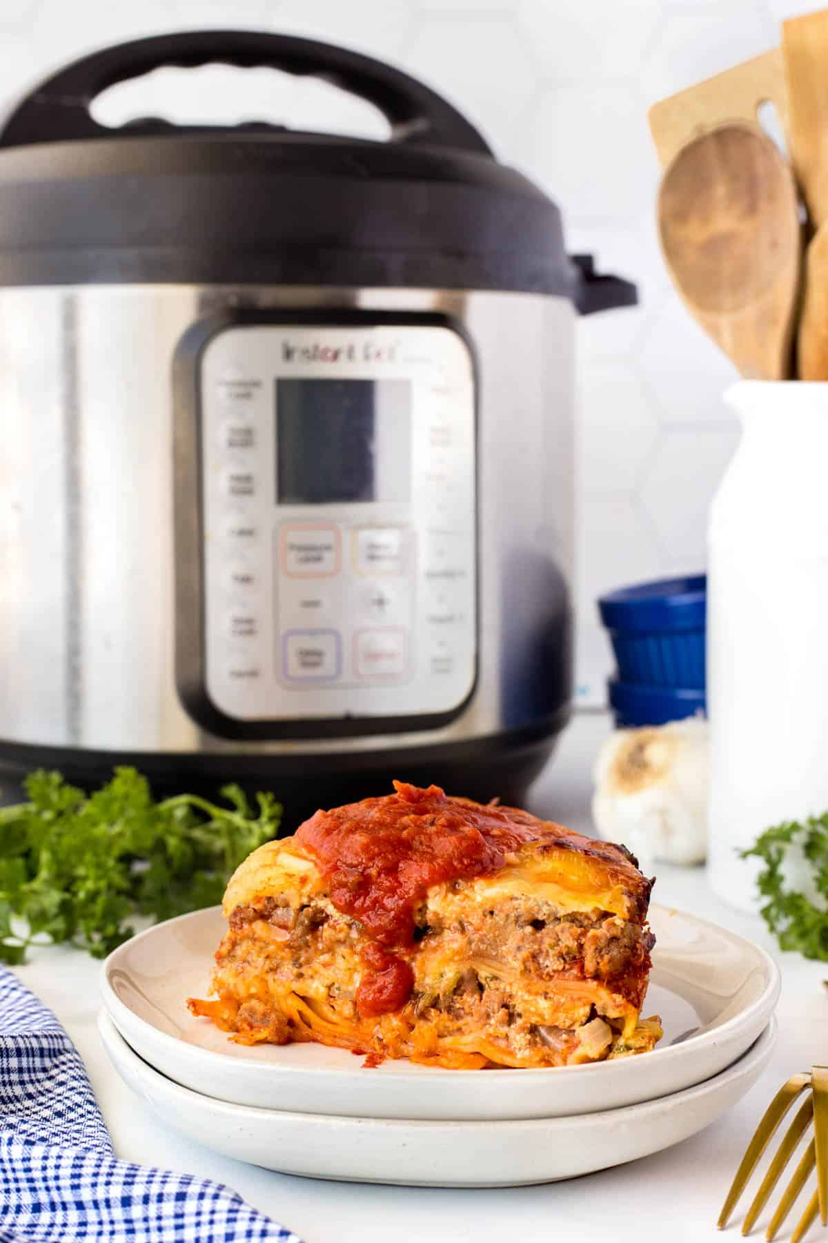 Lasagna on a plate and an Instant Pot in the background
