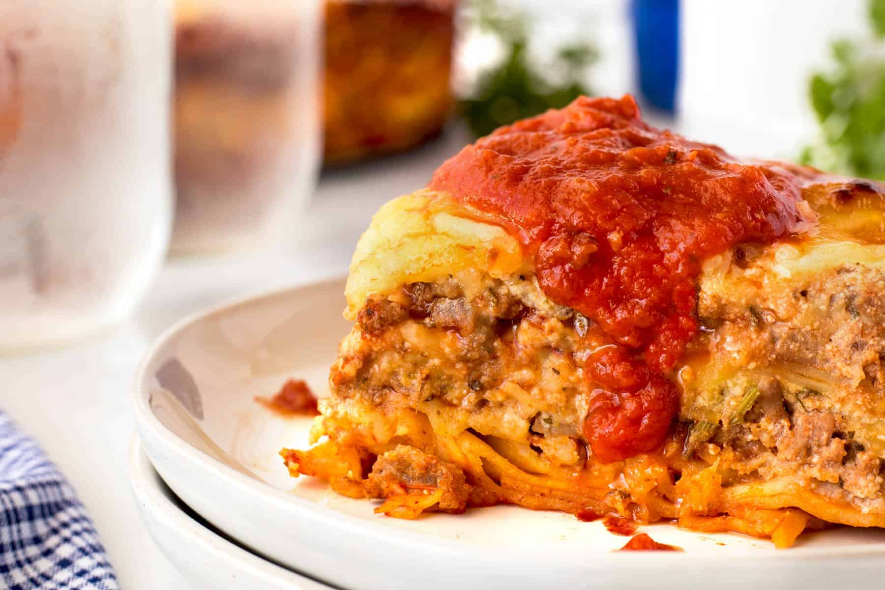Large slice of lasagna topped with marinara sauce