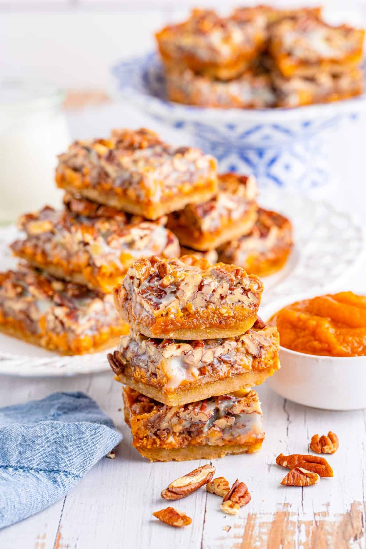 Pecan Magic Pumpkin Bars stacked in three with more in the background and a bowl of pumpkin pie filling at the side.