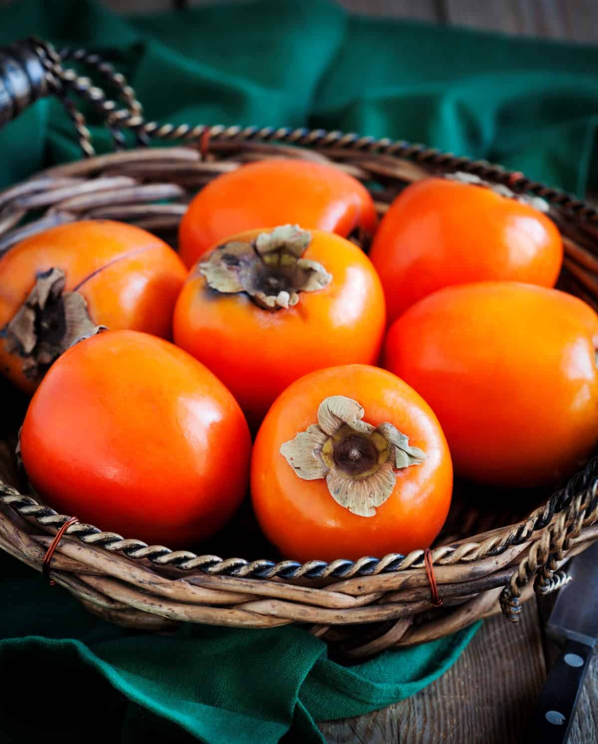 Persimmons in a woven bowl.