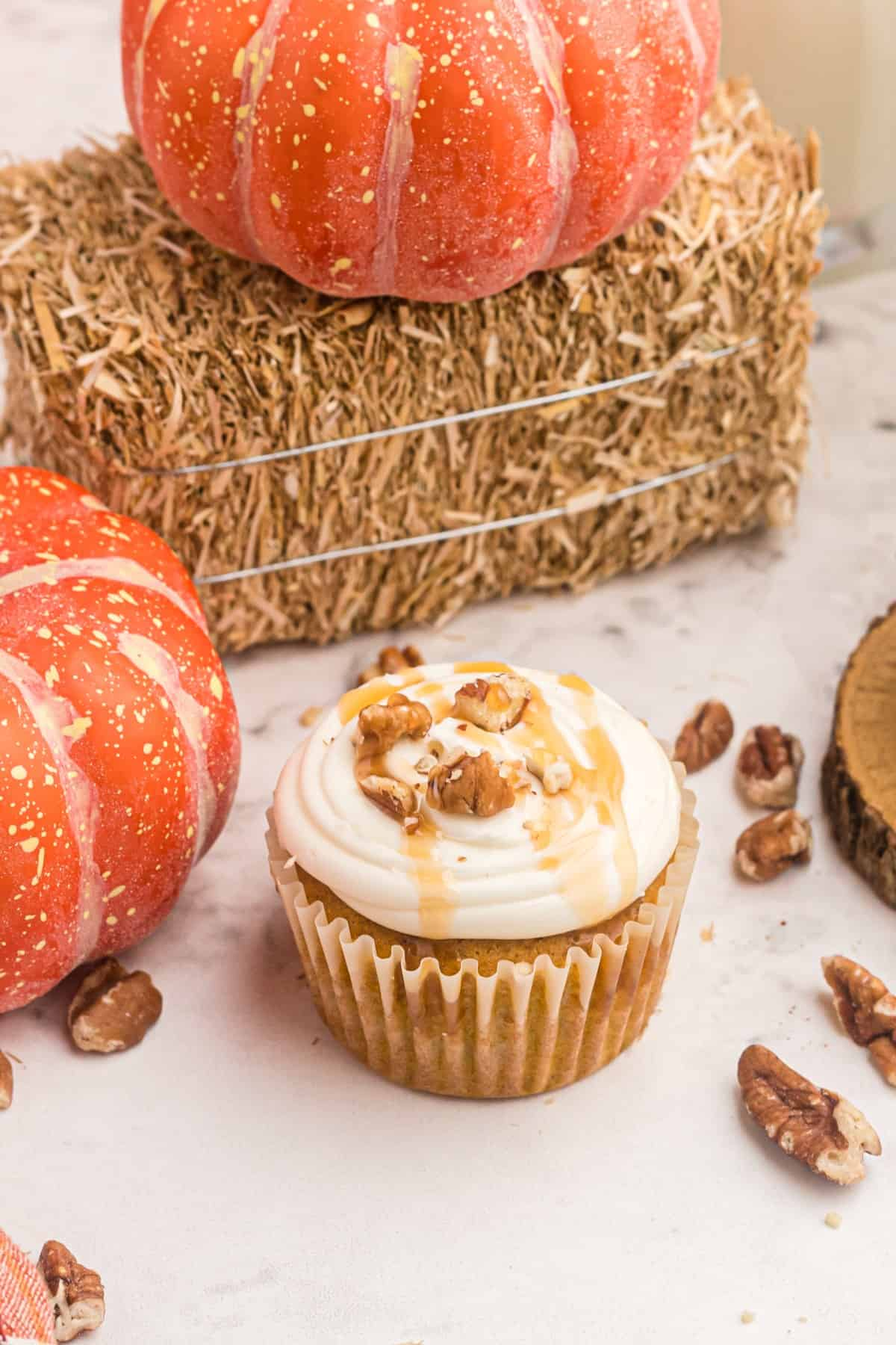 Pumpkin cupcake with pumpkins and hay in background.