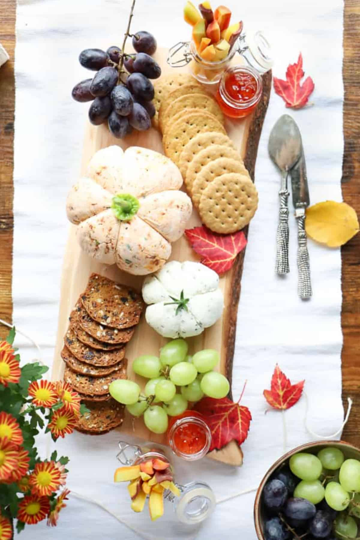 Pumpkin cheese balls on a wooden board with grapes and crackers.