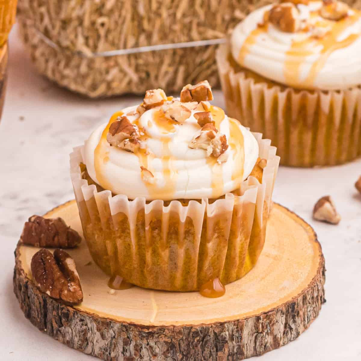 Pumpkin cupcakes drizzled with caramel and walnuts on a wood board.