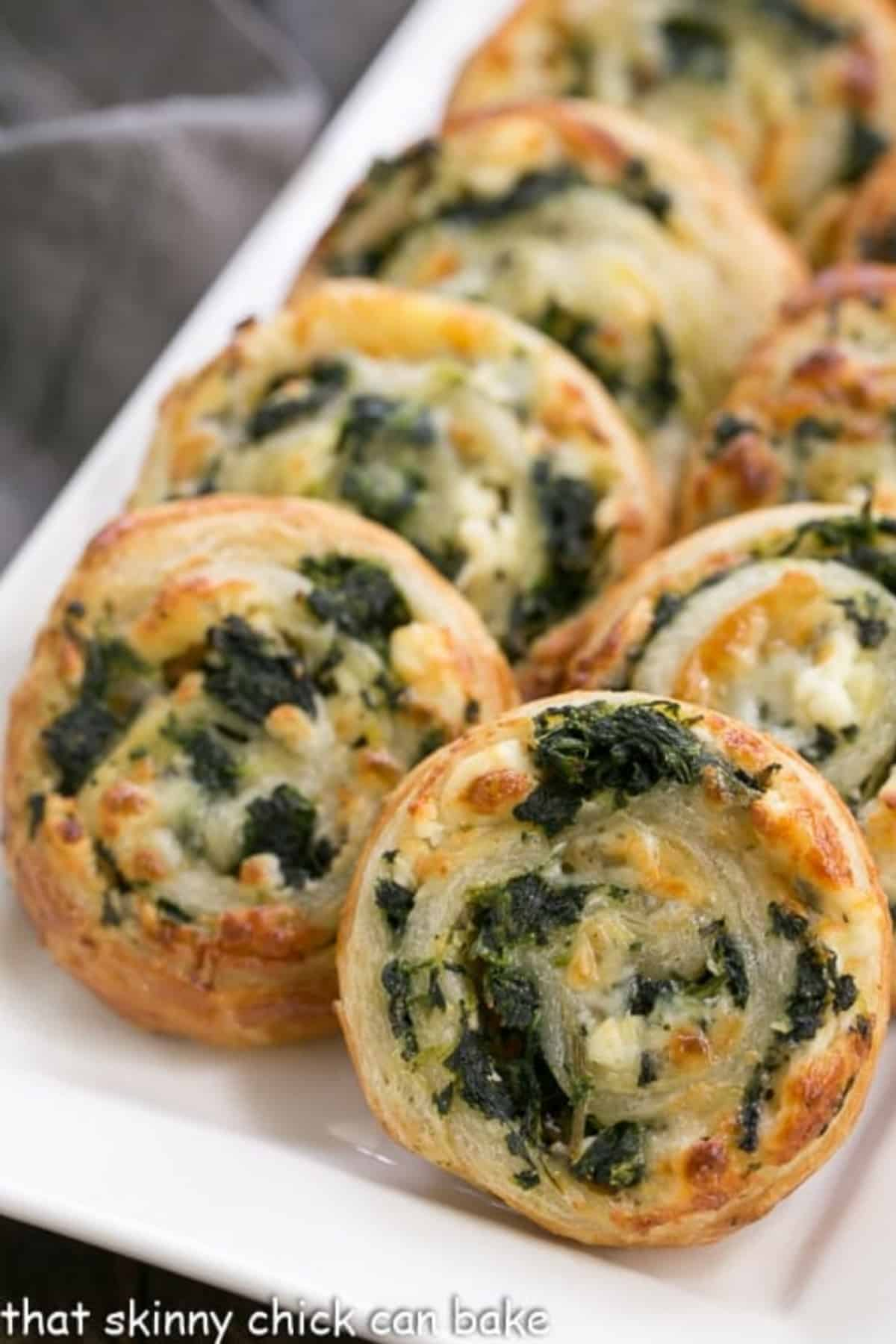 Spinach feta pinwheels lined up on a white platter