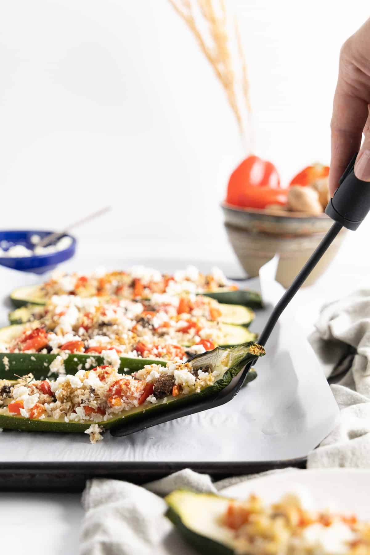 Side view of someone picking a vegetarian stuffed zucchini with serving cutlery