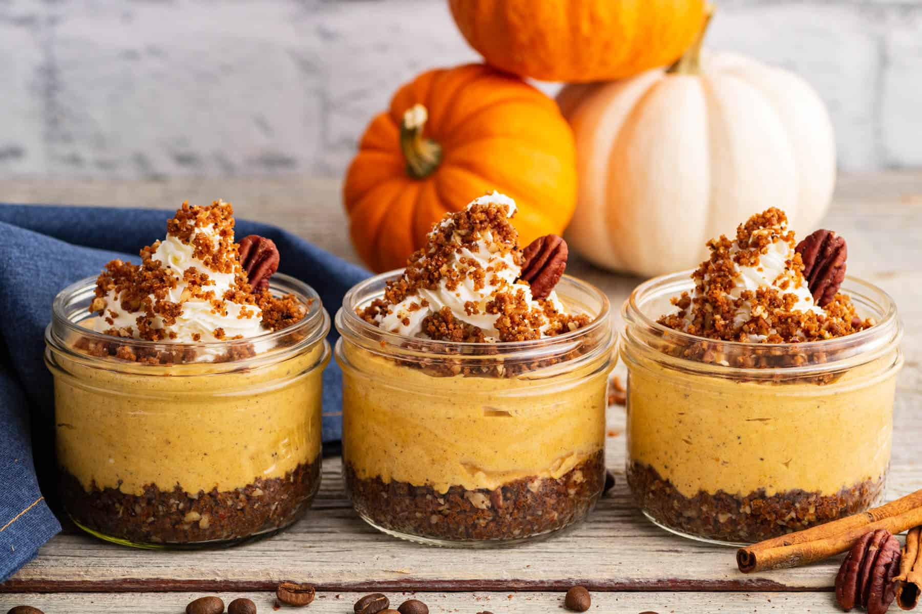 Three individually sized Pumpkin Delight desserts topped with gingersnap crumbs and pecans sit amongst decorative pumpkins.