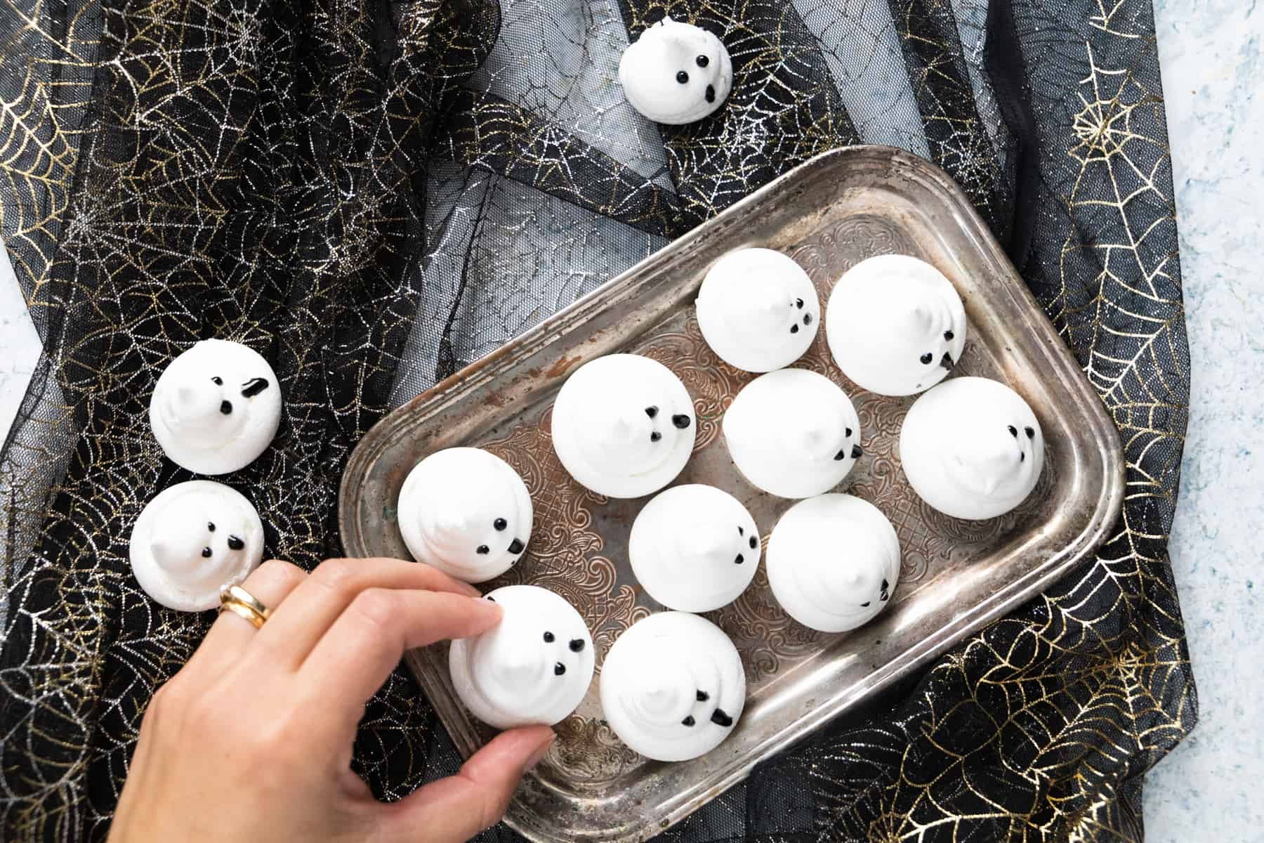 Overhead shot of Meringue Ghosts on a tray, with a hand going to pick one up.