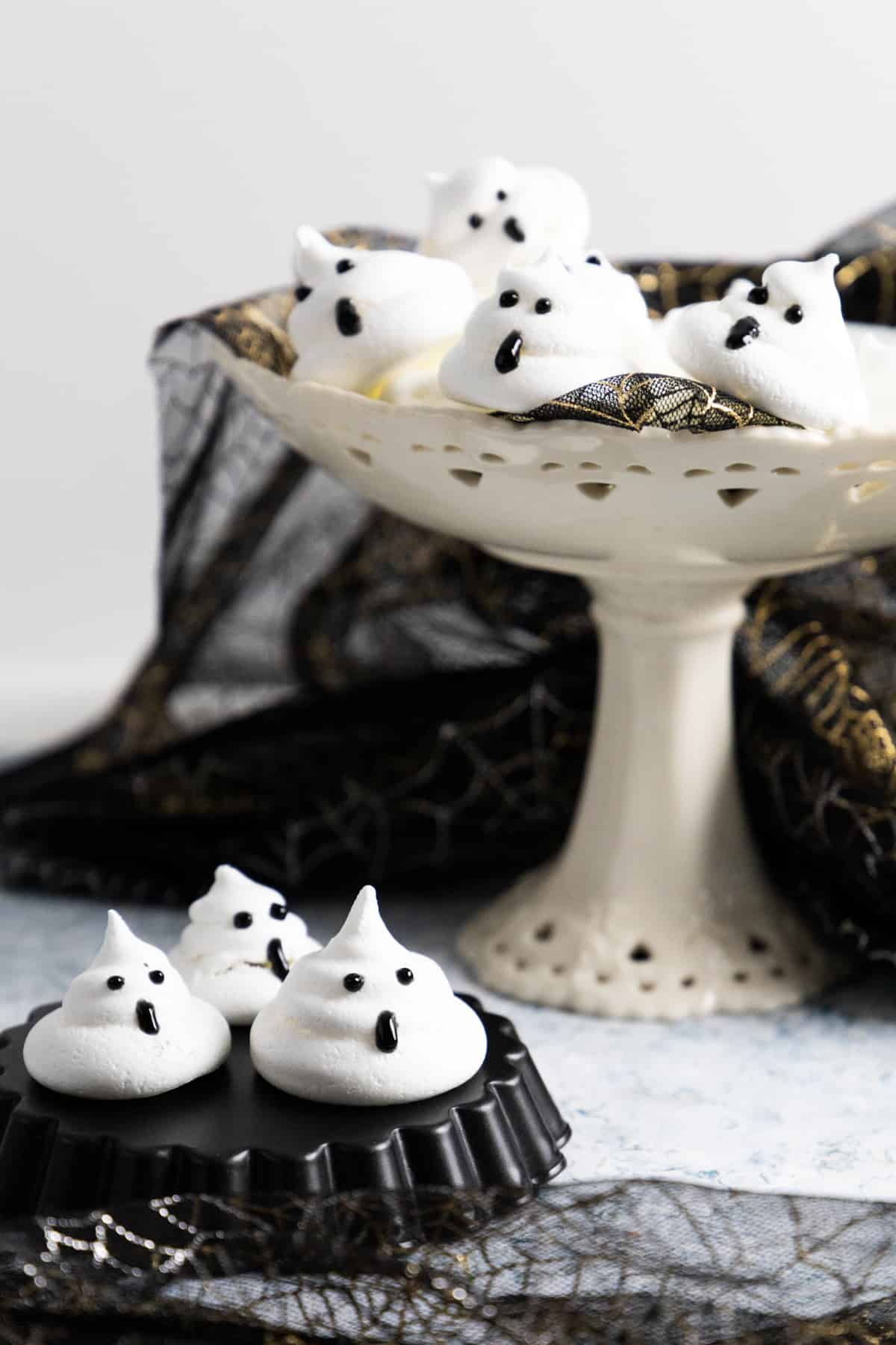 Side view of a cake stand with ghost meringues and a few on a black mold on the table.